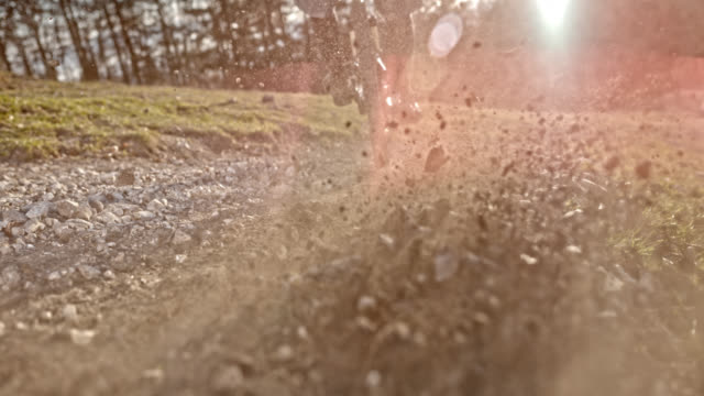 speed ramp mountain biker splashing gravel into the camera in sunshine - andare in mountain bike video stock e b–roll