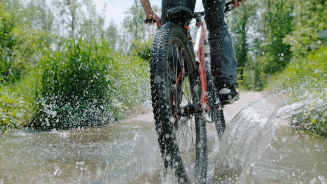 slo mo mountain biker splashing water through a puddle - super slow motion stock videos & royalty-free footage