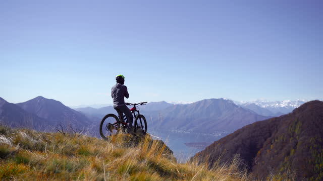 mountain biker strapping on helmet before dropping into trail down mountain - one mid adult man only stock videos & royalty-free footage