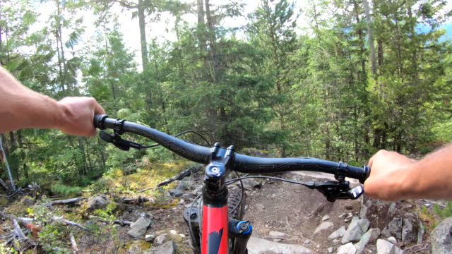vídeos y material grabado en eventos de stock de el ciclista de montaña atraviesa el sendero forestal con agilidad - manillar