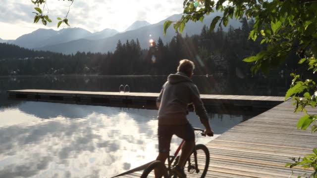 vidéos et rushes de le motard de montagne traverse la jetée de bord de lac au lever de soleil - hommes d'âge mûr