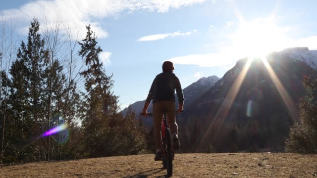 mountain biker traverses meadow, mountains distant - mature men stock videos & royalty-free footage