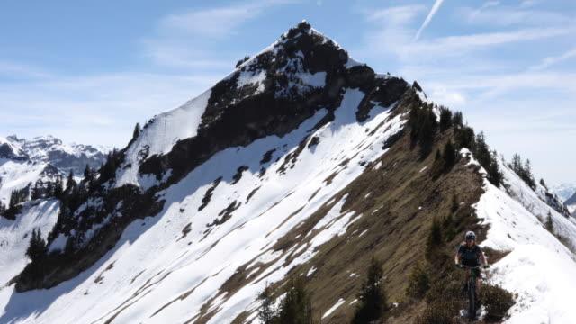 mountain biker traverses narrow ridge beside snow - kopfbedeckung stock-videos und b-roll-filmmaterial