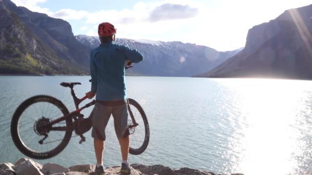 mountainbiker durchquert uferfelsen am see - banff nationalpark stock-videos und b-roll-filmmaterial
