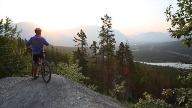 mountain biker traverses to viewpoint at sunrise - mountain biking stock videos & royalty-free footage