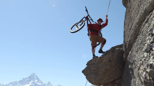 mountain biker uses rope to ascend vertical cliff - abseiling stock videos & royalty-free footage