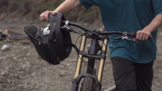 vídeos de stock, filmes e b-roll de a mountain biker walking  his bike in a scenic forest. - super slow motion - filmed at 240 fps - goodsportvideo