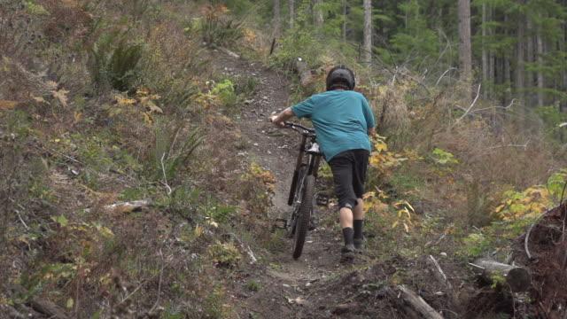 vídeos y material grabado en eventos de stock de a mountain biker walking  his bike with a scenic forest in the background. - super slow motion - filmed at 240 fps - sólo hombres jóvenes