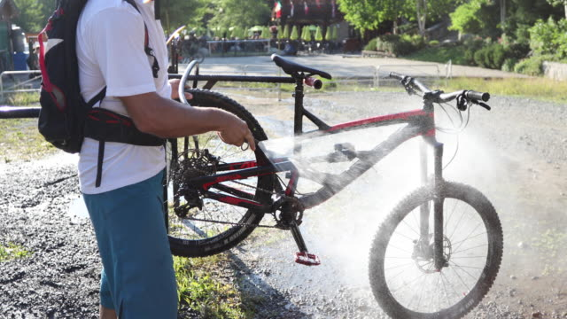 mountain biker washes bike at washing station, after ride - hose stock videos & royalty-free footage