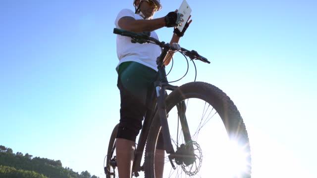 vídeos y material grabado en eventos de stock de ciclista de montaña con tableta digital en una ladera rocosa - accesorio de cabeza
