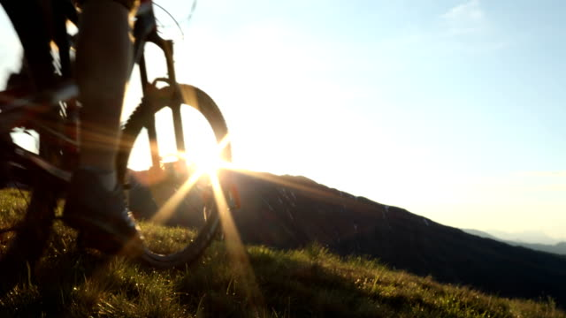mountain bikers ascend alpine slope as sun rises over distant mountains. - hood clothing stock videos and b-roll footage