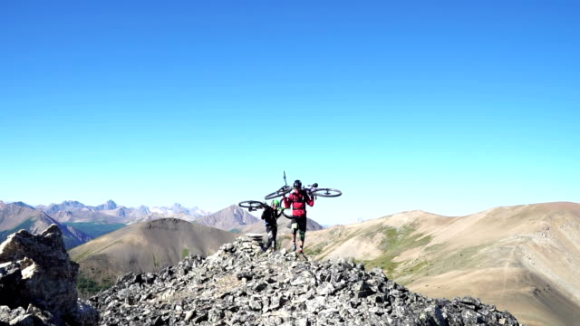 Mountain bikers ascend steep mountain slope, to summit