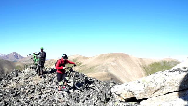 mountain bikers ascend steep mountain slope, to summit - mountainbike stock-videos und b-roll-filmmaterial