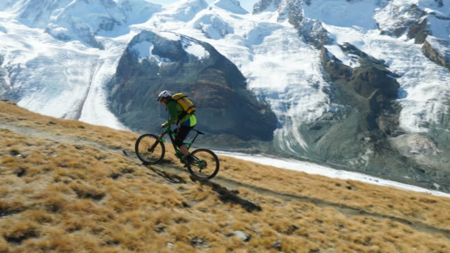 Mountain bikers ascends high alpine trail to lookout over glacier