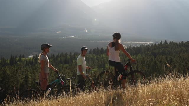 stockvideo's en b-roll-footage met mountainbikers converseren op grasrijke nokkam boven vallei - hoofddeksel
