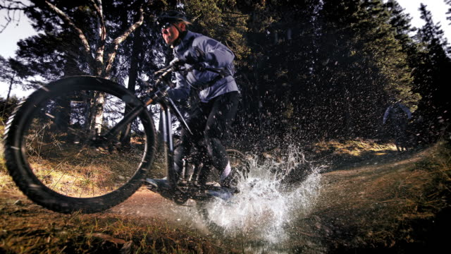 speed ramp mountain bikers crossing a forest puddle making a splash - mountain bike video stock e b–roll
