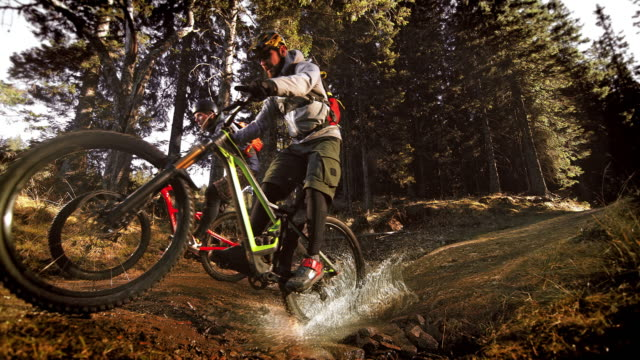 slo mo mountain bikers crossing a muddy puddle in the forest - männerfreundschaft stock-videos und b-roll-filmmaterial