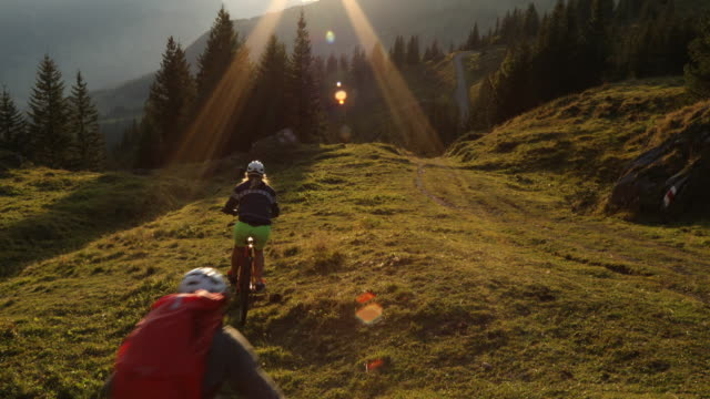 mountain bikers descend alpine meadow towards mountains - der weg nach vorne stock-videos und b-roll-filmmaterial