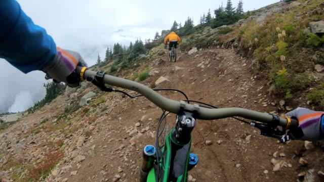 vídeos de stock, filmes e b-roll de ciclistas de montanha descem alta alpino race course em condições atmosféricas - geração z