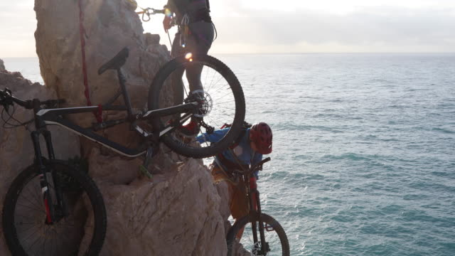 mountain bikers descend step cliff at sunrise - steep stock videos & royalty-free footage