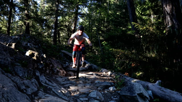Mountain Bikers descend technical rocky slope