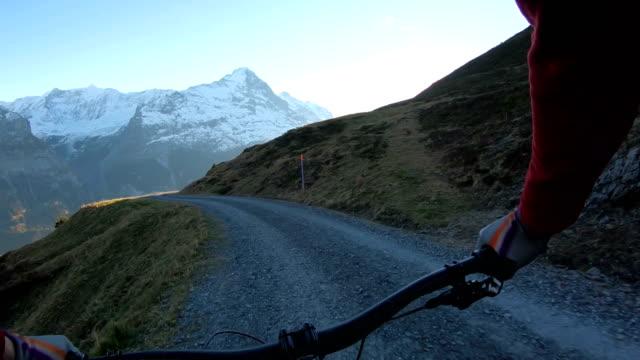 vidéos et rushes de les vététistes descendent à travers les prairies alpines - alpes suisses