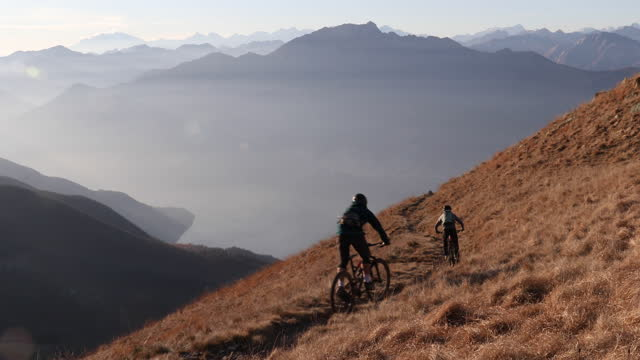 mountain bikers descend trail above lakes and mountains - mountain bike stock videos & royalty-free footage