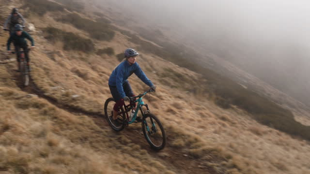 mountain bikers descend trail above lakes and mountains - mountain biking stock videos & royalty-free footage