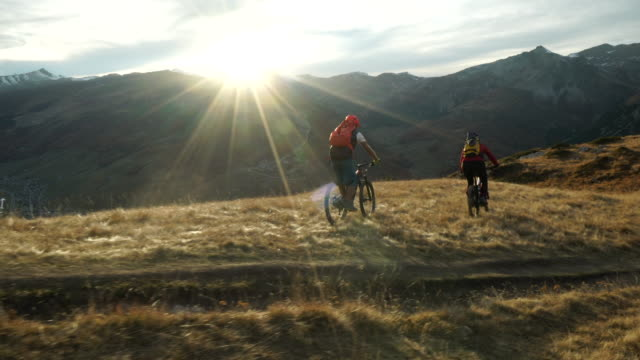 Mountain bikers descending mountain ridge at sunset