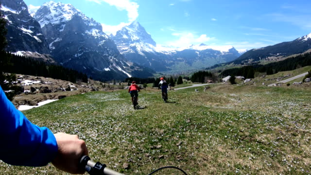 mountain bikers descent alpine slope towards the eiger and the jungfrau group in early spring - sports helmet stock videos & royalty-free footage