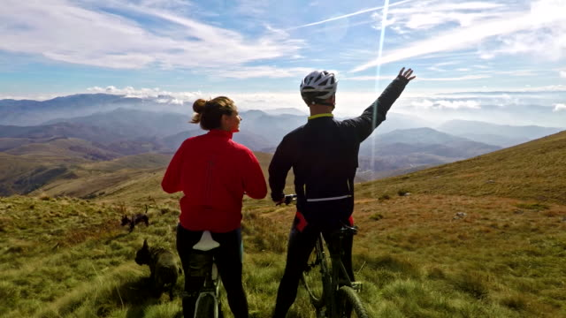 mountain bikers enjoying a view from the ridge 4k - at the edge of stock videos & royalty-free footage