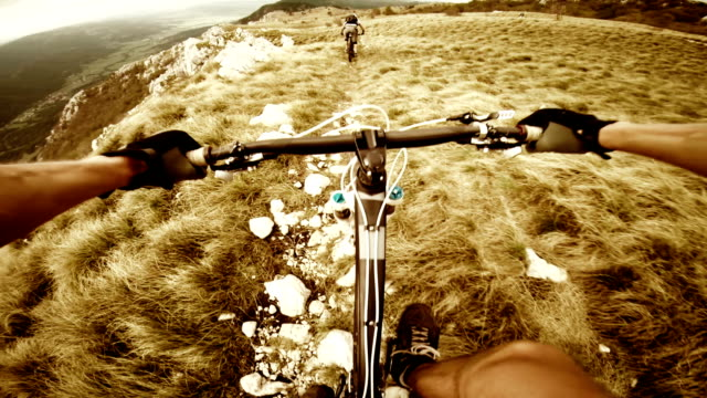 POV Mountain bikers gives thumb up and rides the ridge