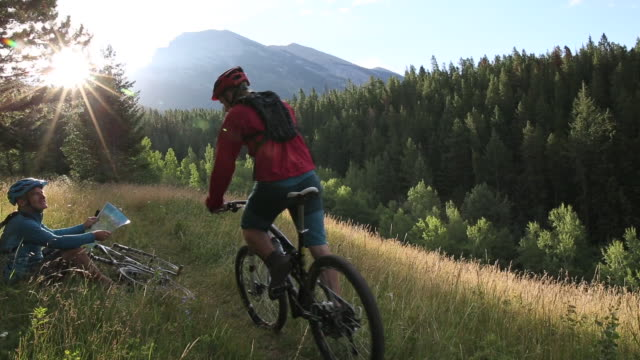 stockvideo's en b-roll-footage met mountain bikers pause in meadow to check map, take smart phone pic - mountainbiken fietsen