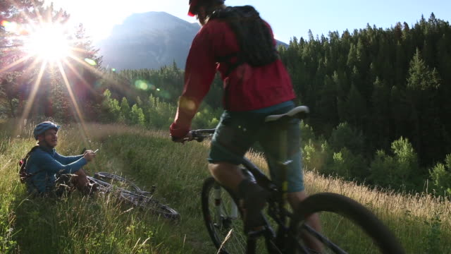 Mountain bikers pause in meadow to check smart phone, converse