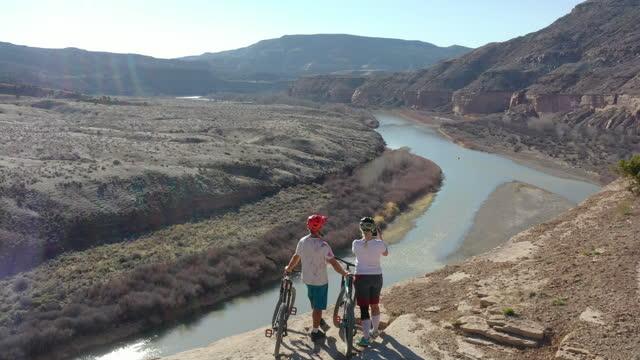 mountain bikers pause on river overlook, take photo - mountain biking stock videos & royalty-free footage