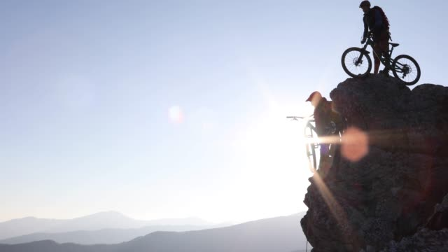 vidéos et rushes de les vététistes se préparent à descendre du sommet du rocher - danger