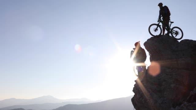 Mountainbikers voorbereiden om af te dalen van de top van de rots