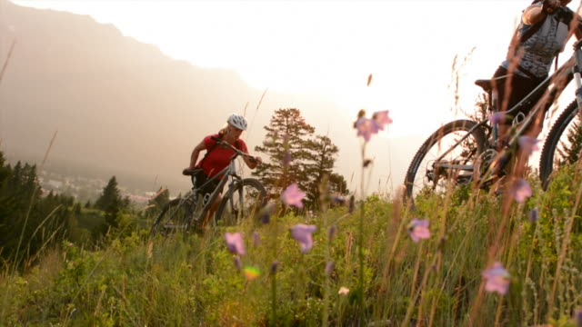 mountain bikers push bikes up steep mountain slope, sunrise - steep stock videos & royalty-free footage
