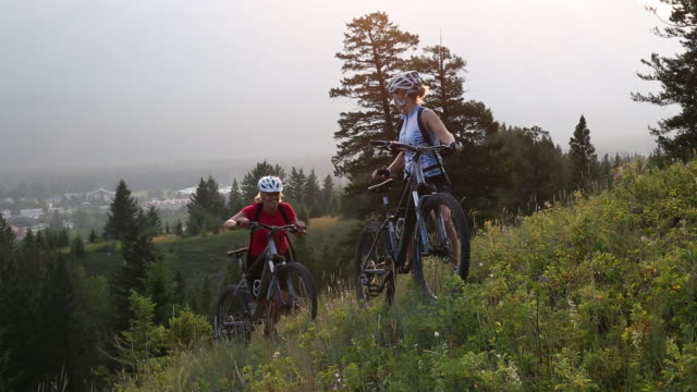 stockvideo's en b-roll-footage met mountain bikers push bikes up steep mountain slope, sunrise - rijwiel
