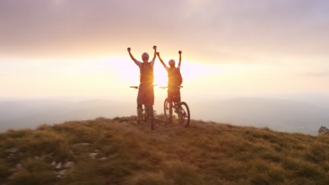 PAN mountain bikers reaching the top at sunset