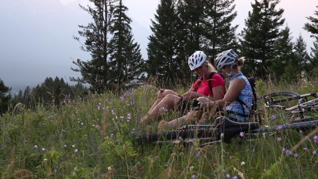 Mountain bikers relax in mountain meadow, taking smart phone pics