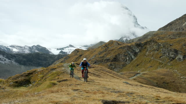 Mountain bikers ride high alpine trail below Matterhorn