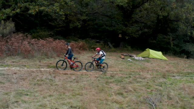 mountain bikers ride through autumn field - carrellata video stock e b–roll