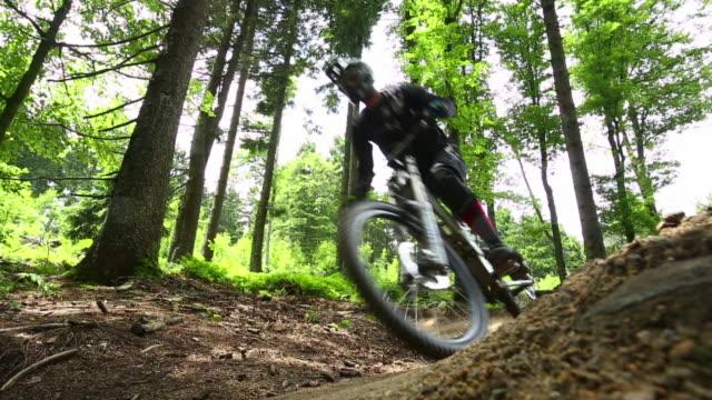 mountain bikers riding downhill in green forest - 未舗装点の映像素材/bロール