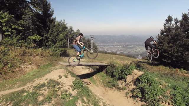aerial mountain bikers riding on a downhill trail - mountain biking stock videos & royalty-free footage
