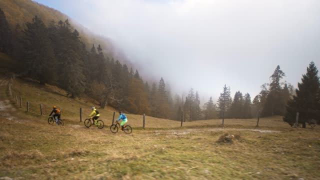 mountain bikers riding on a mountain path with fog coming up from the valley - wide stock videos and b-roll footage