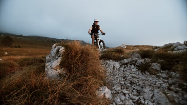 SLO MO mountain bikers riding over rocks