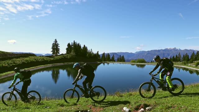 mountain bikers riding past lake in slow motion - named wilderness area stock videos & royalty-free footage
