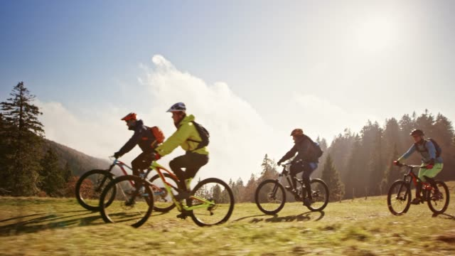 ts mountain bikers riding up a mountain across a meadow in sunshine - mountain bike video stock e b–roll