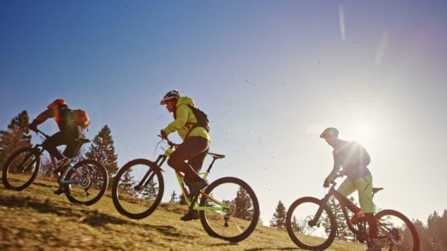 vidéos et rushes de slo mo ts vététistes cheval vers le haut de la prairie de montagne ensoleillé - faire du vélo tout terrain